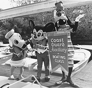 Donald Duck, Mickey Mouse and Goofy hold a banner for Coast Guard Auxiliary Boating Class